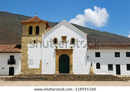 Colombia, Beautiful white villa with shingle roofs hidden behind walls in colonial Villa de Leyva. Parish church on the plaza central - stock photo