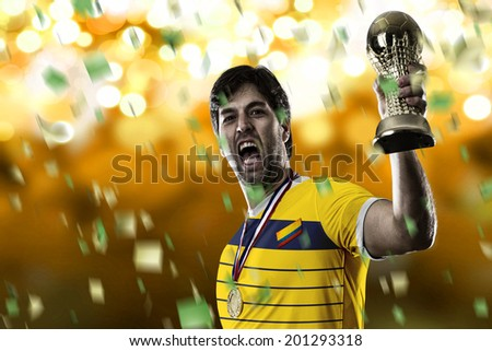 Colombian soccer player, celebrating the championship with a trophy in his hand. On a yellow lights background.