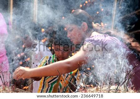 COLOMBO,  SRI LANKA - DEC 11: An unidentified Buddhist  devotee burn incense sticks as a religious ritual at the Kelaniya Raja Maha Vihara on December 11, 2013 in Colombo, Sri Lanka.  - stock photo