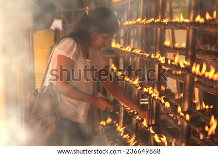 COLOMBO,  SRI LANKA - DEC 11: An unidentified Buddhist  devotee lights up flames as a religious ritual at the Kelaniya Raja Maha Vihara on December 11, 2013 in Colombo, Sri Lanka.  - stock photo