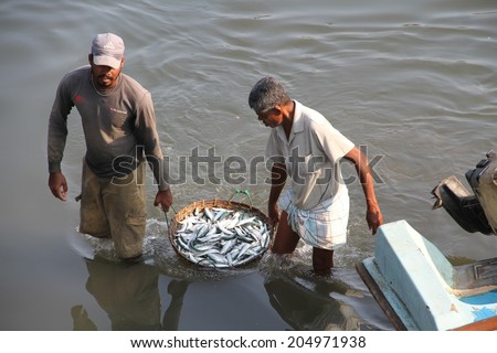 COLOMBO, SRI LANKA - MARCH 1: Two fishermen carrying a basket of fish in the lagoon near the fish markets of Negombo, near Colombo, Sri Lanka on the 1st March, 2014. - stock photo