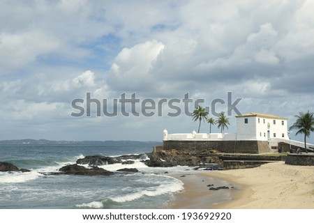 Colonial Fort Santa Maria in Barra Salvador Brazil built on tropical beach with palm trees - stock photo