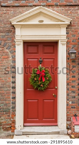Colonial red doorway in historic Elfreth's Alley in Philadelphia with pediment and  christmas wreath. - stock photo