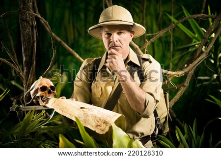 Colonial style pioneer in the jungle examining an old map and searching for the right direction. - stock photo