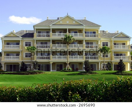 colonial yellow resort hotel with professional landscaping on golf course