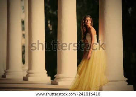 colonnade of the old-time building and gorgeous bride in the white-golden gown, instagram image style
