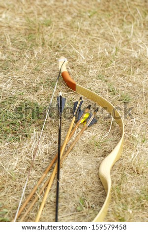 color archery arrows and bow in nature on the ground - stock photo