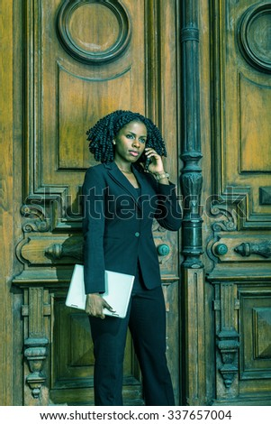 Color #01B1AE filtered look. African American Businesswoman working in New York. Young black female lawyer with braid hairstyle standing by doorway, carrying laptop computer, listening cell phone. - stock photo