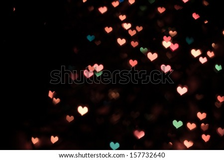 Color Bokeh on a dark background with hearts  - stock photo