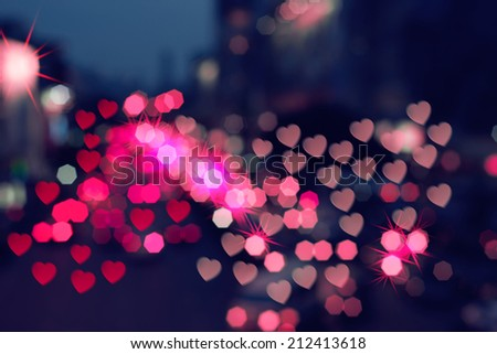 Color Bokeh on a dark background with hearts for backgrouds. - stock photo