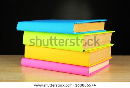 color books on table on black background - stock photo