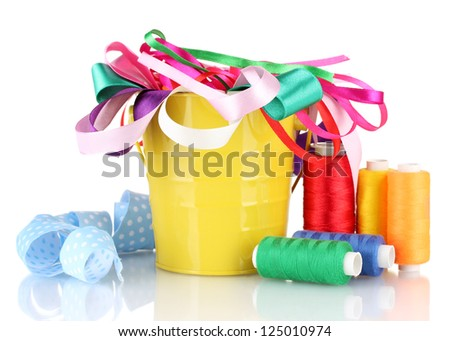 Color bucket with multicolor ribbons and thread isolated on white