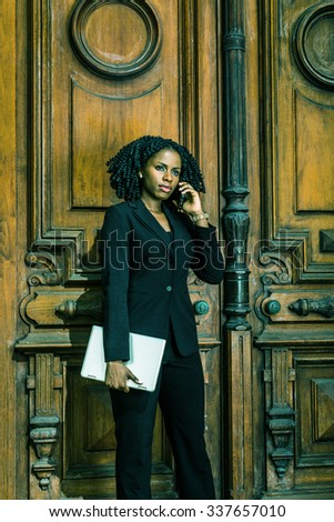 Color #40C1AC filtered look. African American Businesswoman working in New York. Young black female lawyer with braid hairstyle standing by doorway, carrying laptop computer, listening cell phone. - stock photo