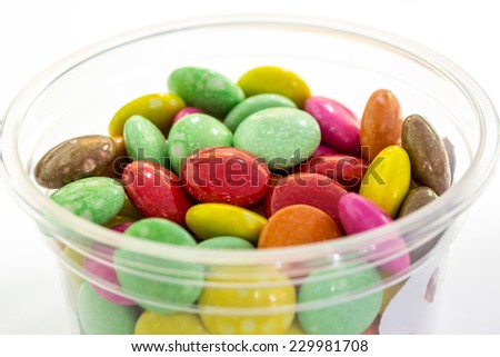 Color candy in cup on white
