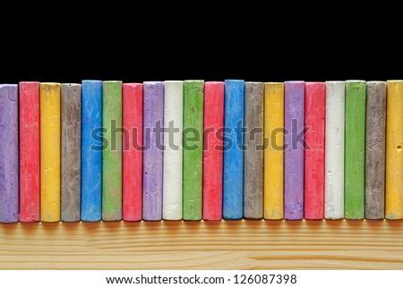Color chalks arranged in line on blackboard - stock photo