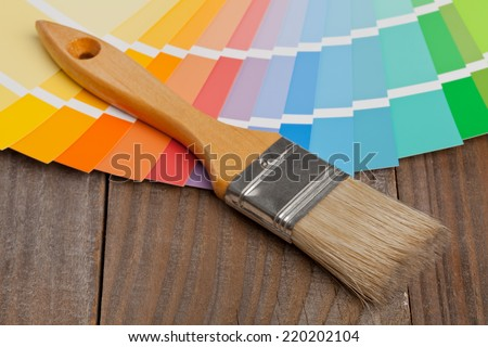 Color chart guide for renovation with brush on wooden surface - stock photo