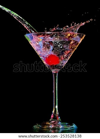 Color cocktail with a cherry splash in a martini glass - stock photo