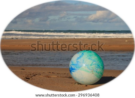 color concept image for global environmental issue using inflatable rubber ball with earth like markings against ocean beach background shaped format  - stock photo
