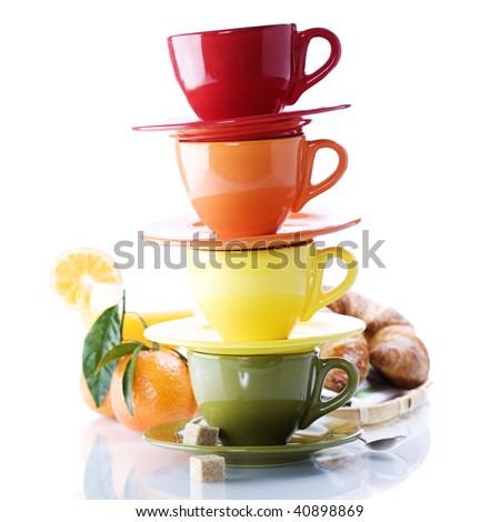 Color cups, croissants and orange juice on white background