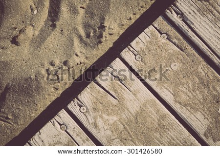 Color detail of a vintage deck and sand by the beach