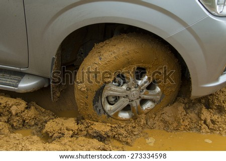 Color detail shot of an off-road car's wheel, covered in mud, Nissan NP300 Navara car. - stock photo