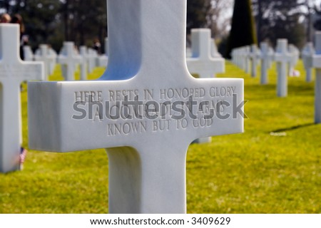Color DSLR image of cross headstone at the burial grave of an unknown soldier at the Normandy American Cemetery, France.  Many of the WWII dead american heroes lie in this landmark memorial.  - stock photo