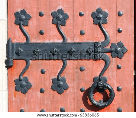 Color DSLR image of macro detail on decorative and ornate black wrought iron hinge on a red wood door; in horizontal orientation - stock photo