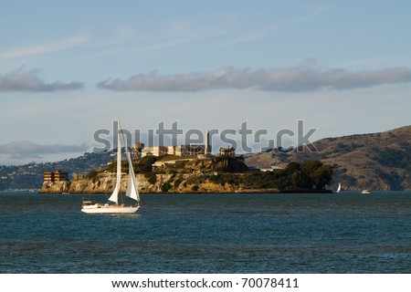 Color DSLR image of The Rock, Alcatraz in San Francisco harbor, California with a white sailboat floating in the breeze, in horizontal orientation with copy space for text - stock photo