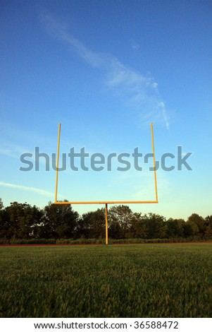 Color DSLR image of yellow American sports football goal posts on a green grass field and a blue sky background. At dusk. Vertical with copy space for text. - stock photo