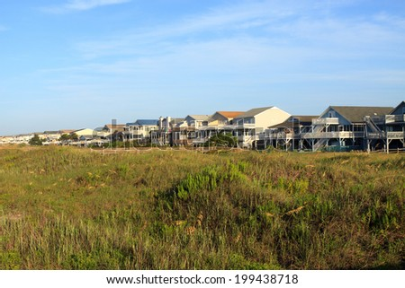 Color DSLR landscape picture of luxury beach vacation houses across the green sand dunes, in Sunset Beach, North Carolina.  The image is in horizontal orientation with ample copy space for text.