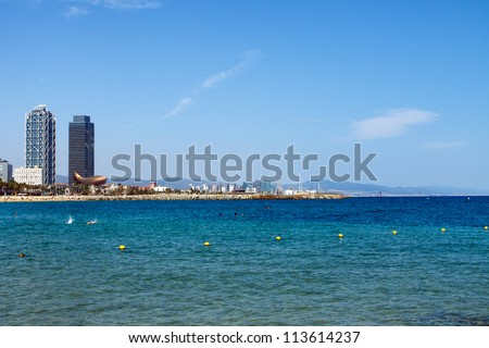 Color DSLR landscape picutre of skyscrapers on the Mediterranean Sea in Barcelona, Spain.  The buildings are in the distance, framing the water.  In horizontal orientation with copy space for text
