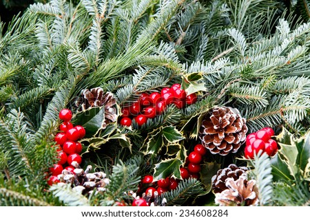 Color DSLR picture of a festive Christmas holiday wreath, with green holly, pine and cones, with red berries.  The decoration in in horizontal orientation. - stock photo