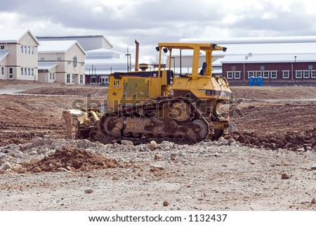 Color DSLR picture of a yellow bulldozer at an outdoor construction site.  The unfinished building is behind the heavy equipment.  The image is in horizontal orientation with copy space for text.