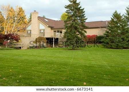 Color DSLR picture of back of a suburban colonial house, in the fall.  The green grass is open.  Horizontal orientation with copy space for text - stock photo