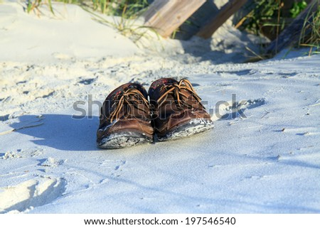 Color DSLR picture of brown leather boat shoes in the white sand at the beach.  The docksiders are lit by sunlight.  The image is in horizontal orientation with copy space for text - stock photo