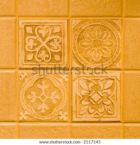 Color DSLR picture of decorative kitchen tiles in a backsplash.  The four center square tiles have different patterns.  Copy space for text. Background, decoration or construction image. - stock photo