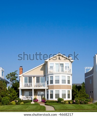 Color DSLR picture of isolated luxury vacation beach house on the New Jersey shore.  Green grass lawn and a clear blue sky background. Vertical orientation with copy space for text. - stock photo