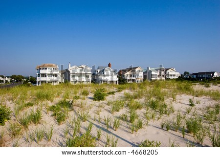 Color DSLR picture of luxury vacation beach houses along the New Jersey shore, with grass covered sand dunes in the foreground and clear blue sky background. Horizontal with copy space for text. - stock photo