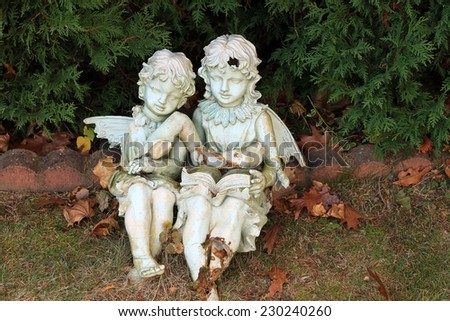 Color DSLR picture of small broken garden cherubs sitting on a bench.  The background is green grass and shrubs.  The image is in horizontal orientation with copy space for text - stock photo