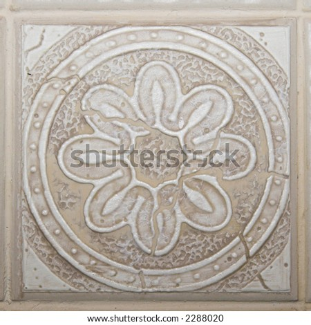 Color DSLR picture of square off white, tan or beige decorative ceramic tile with flower pattern and relief texture. - stock photo
