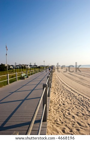 Color DSLR picture of wooden boardwalk along the beach on New Jersey shore.  Sand and surf on the right and grass covered sand dunes on left. Clear blue morning sky. Vertical with copy space for text