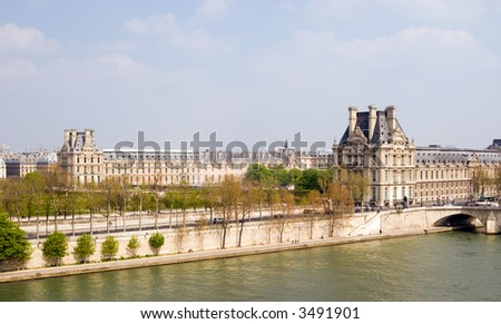 Color DSLR wide angle view of the Louvre Museum, across the flowing Seine River, Paris, France. The ancient landmark houses some of the worlds most famous art. Horizontal with copy space for text.