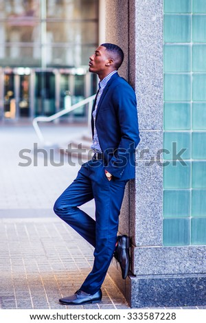 Color #2E1A47 filtered look. African American businessman working in New York. Wearing blue suit, leather shoes, a young black guy standing against wall on street, looking up, sad, deeply thinking.   - stock photo