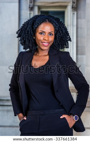 Color #1F2A44 filtered look. African American Business Woman working in New York. Wearing blazer, wristwatch, young pretty black lady with braid hairstyle standing by office building, smiling. - stock photo