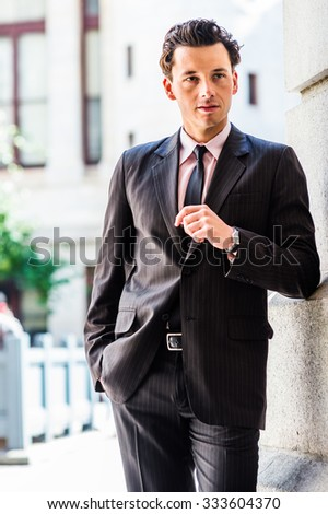 Color #1F2A44 filtered look. Portrait of American Businessman. Dressing formally in suit, necktie, wristwatch, a man standing against wall outside office building on street, looking away, thinking. - stock photo