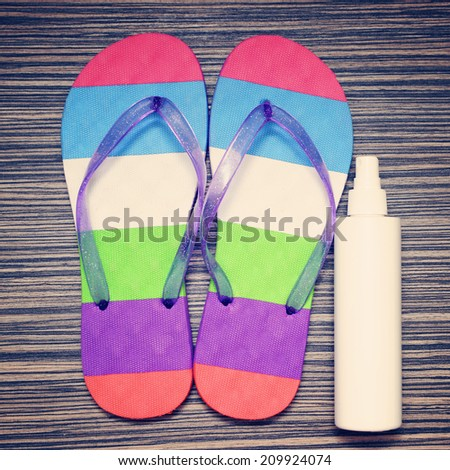 color flip-flop and beach items on wooden background