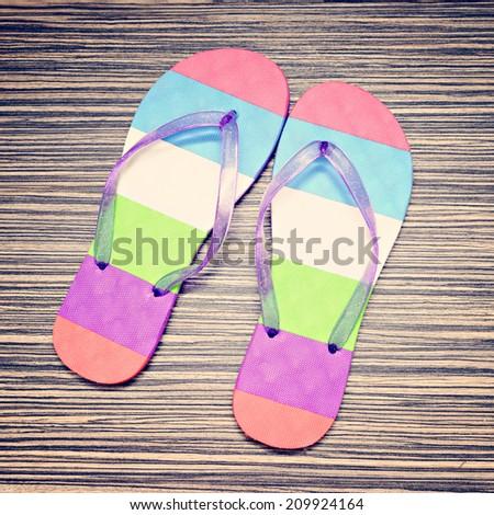 Color flip-flops on wooden floor. Top view. - stock photo