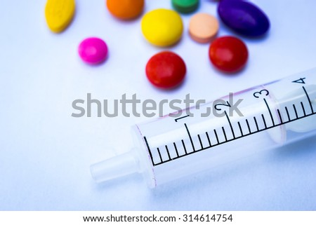 Color full of medicines and syringe on a white background. - stock photo