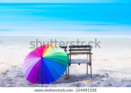 Color full umbrella with wood chairs on the beach - stock photo
