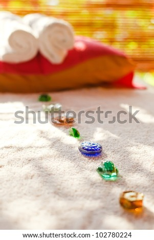 color glass stones on massage table in spa-salon - stock photo